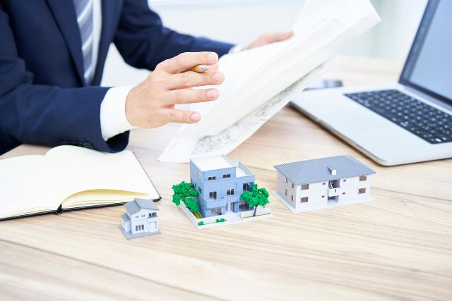 家の模型を見せ説明するビジネスマン