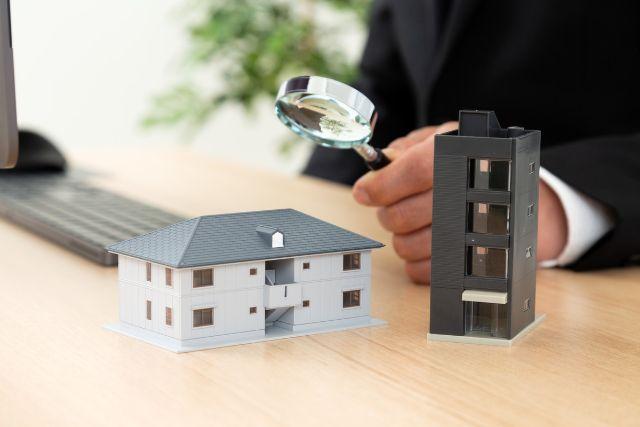 一戸建てやマンションの模型を虫眼鏡で見るビジネスマン